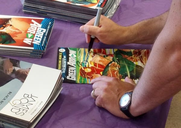 Ben Percy signs the cover of one of his books at Hot Comics.