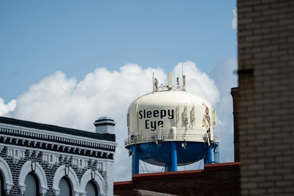 """A water tower that reads """"Sleepy Eye"""" stands over a small town."""