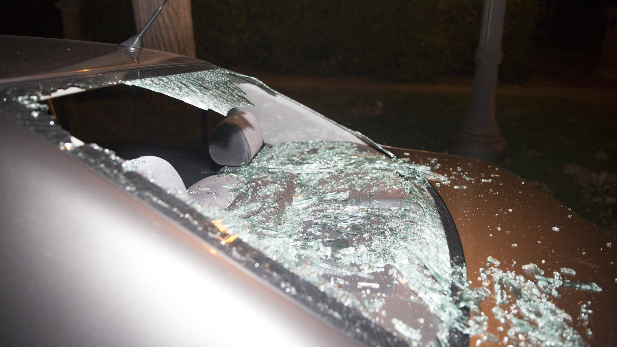A protester smashed the window of a car.