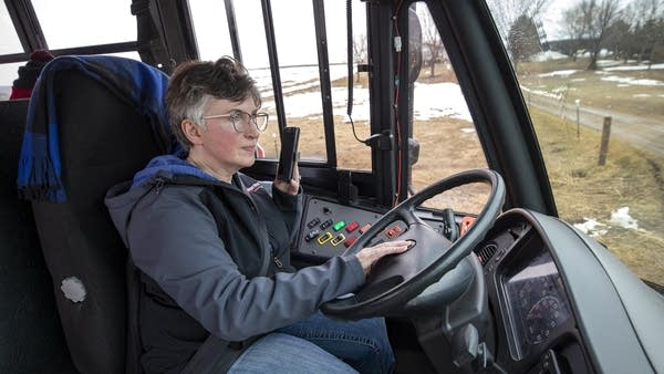 A person talking on the phone while sitting in the driver's seat on a bus.