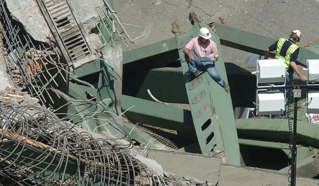 Investigators inspect the collapsed wreckage of the I-35W freeway bridge.