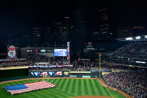 A giant american flag stretches across the outfield with a skyline behind.