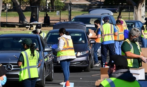 Drivers in their vehicles wait in line at a food distribution event.