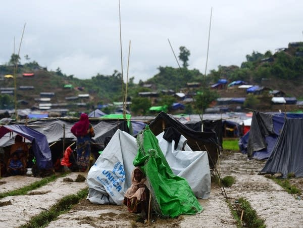 A Rohingya woman sits next to a newly built shelter