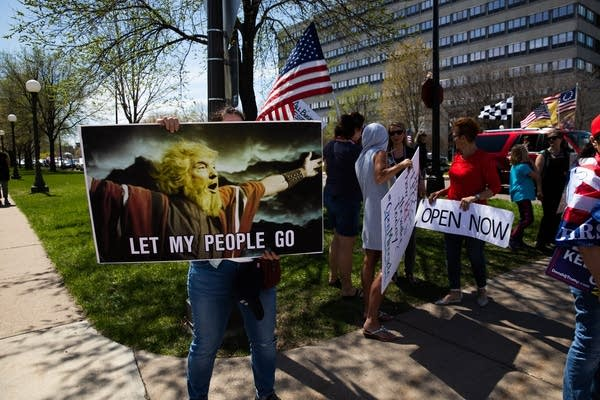 A person holds a sign depicting the president as Moses