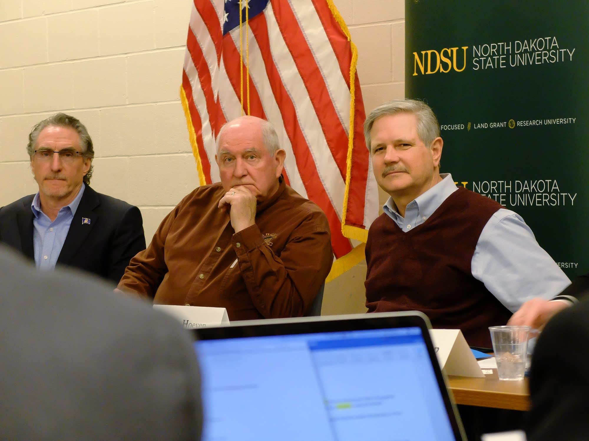 U.S. Agriculture Secretary Sonny Perdue, center, listens to a farmer.