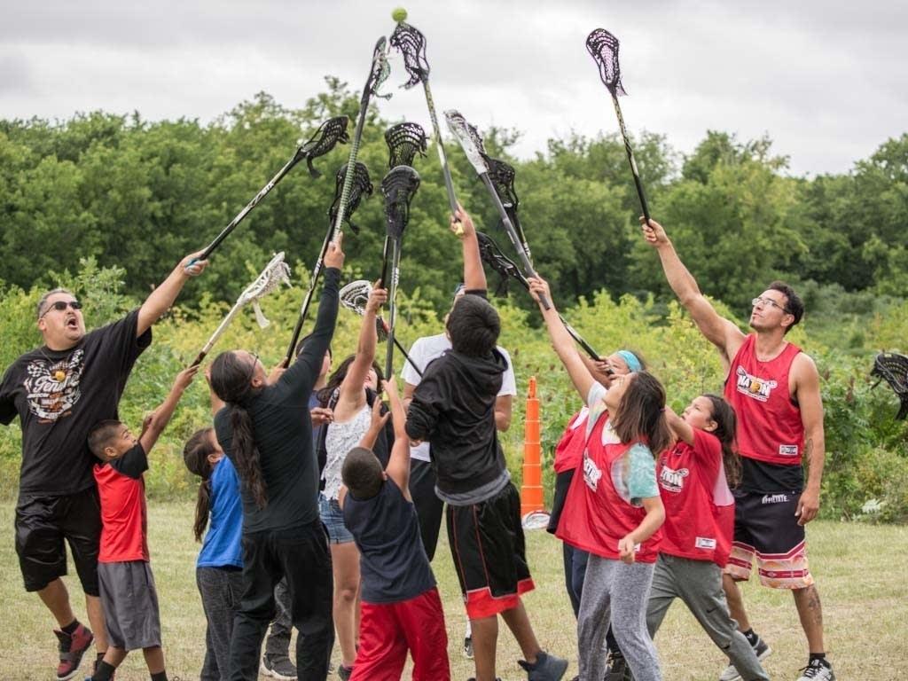 Lacrosse players raise their sticks.