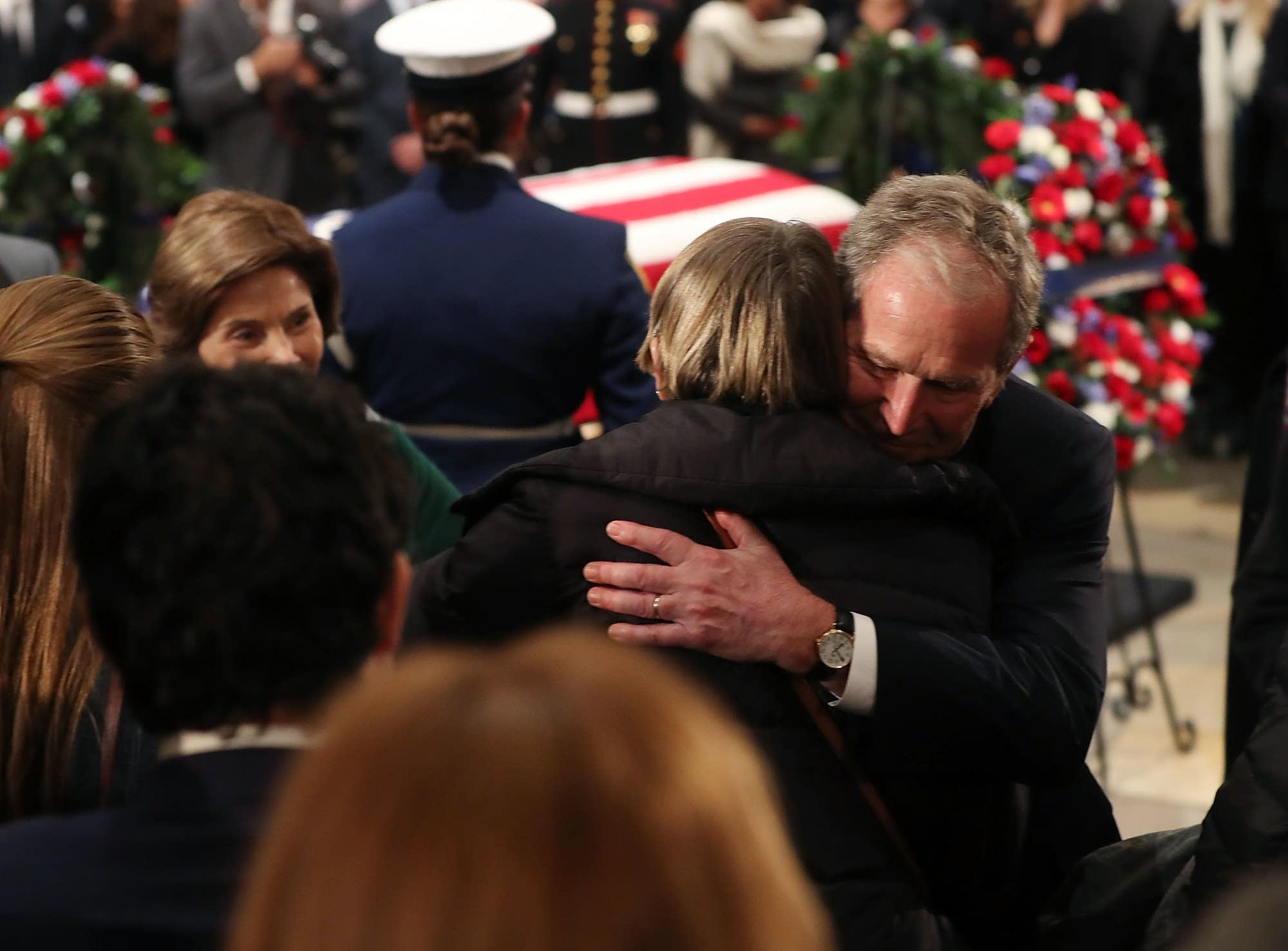 Former President George W. Bush and his wife Laura Bush greet mourners.