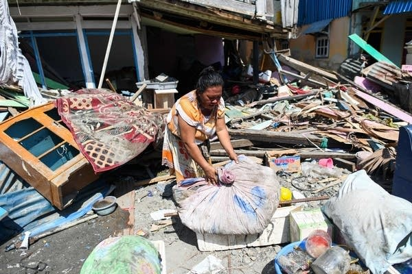A quake survivor salvages items from the debris of a house.