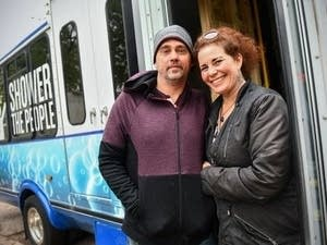 Jason Jaques and Nancy Dyson stand next to their mobile shower van.