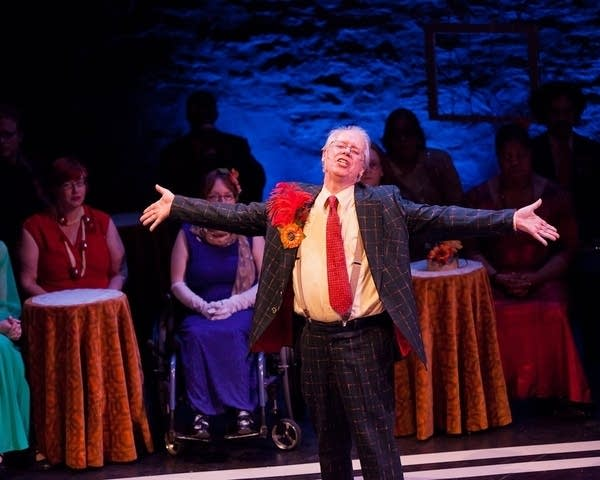 A man in a suit sings with arms outstretched