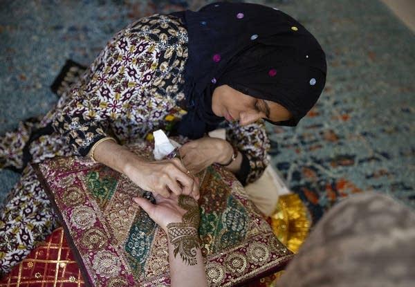 Hajira Begum draws an Indo-Arabic henna design on Faiza Zuckerman's palm.