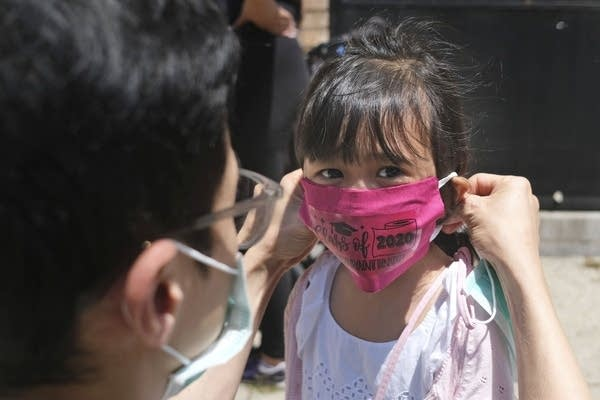A father helps his daughter wear a mask.