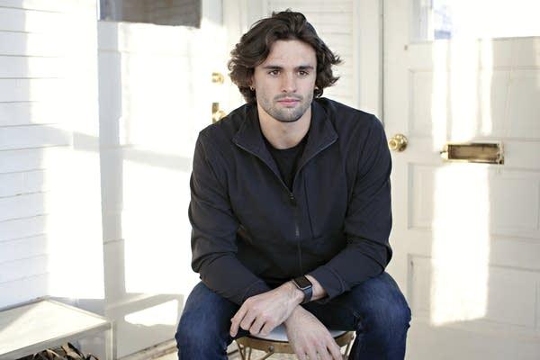 A man sits on a stool.
