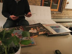 Jim O'Neill examines an LP from a vinyl collection he inherited.