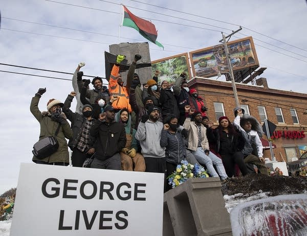 A group of people raise their fists as they stand in front of a sculpture.