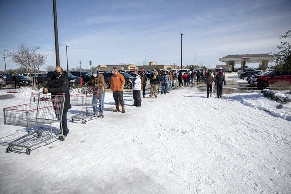 People wait in line at a grocery store in the snow.