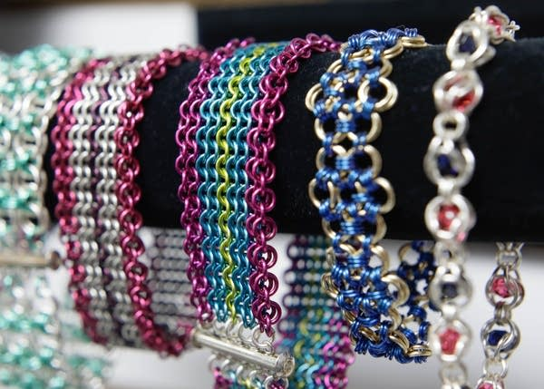 Colorful bracelets made with the chainmaille rings are displayed.