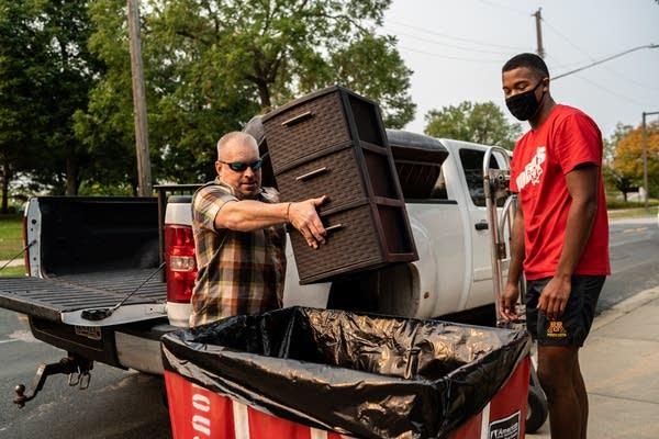 A man puts a file cabinet in a bin.