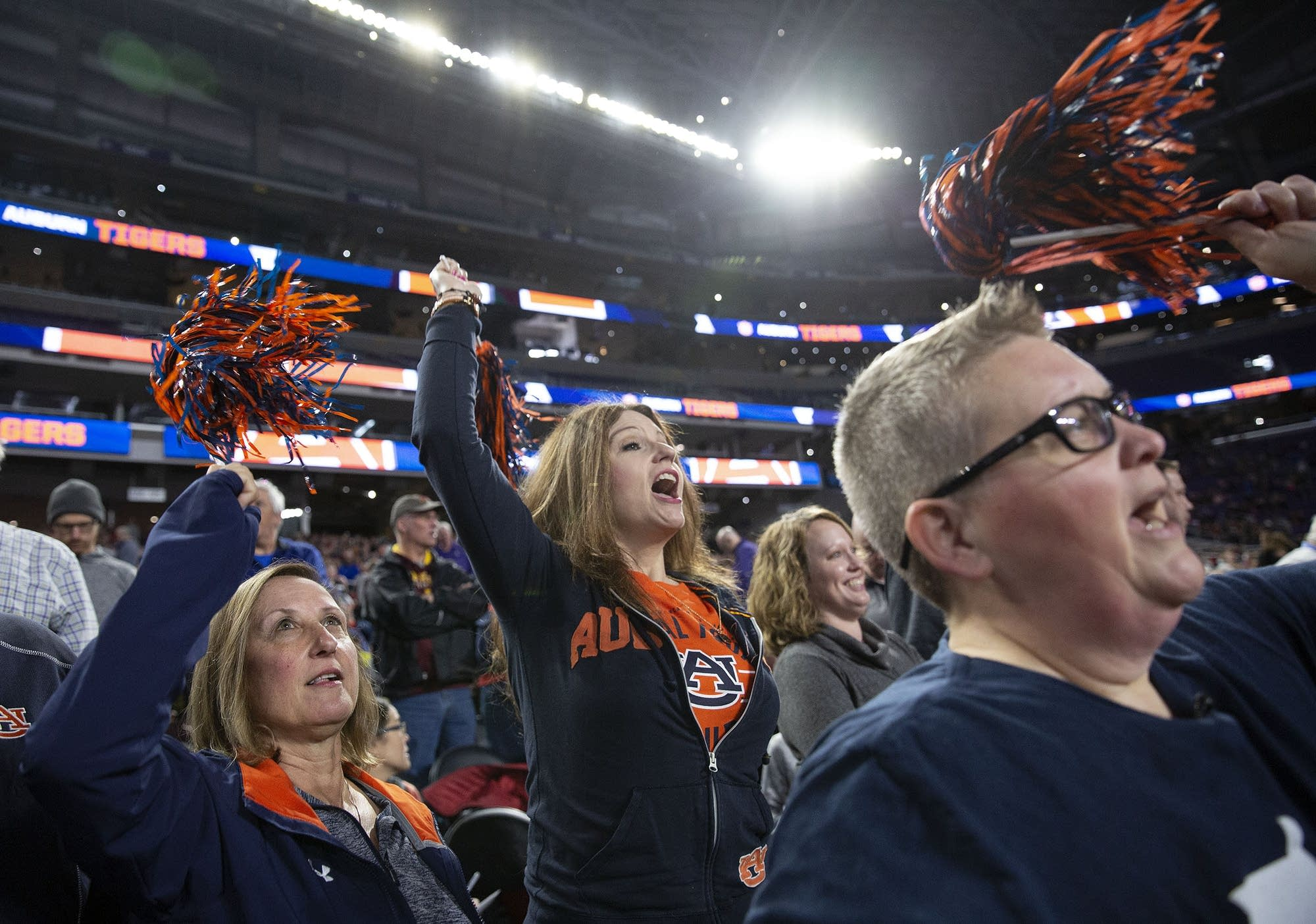 Bobbi Hoebelheinrich, Autumn Toussaint and Chris Turner cheer for Auburn.