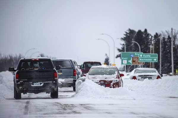 Motorists maneuver around abandoned vehicles stuck in the snow.
