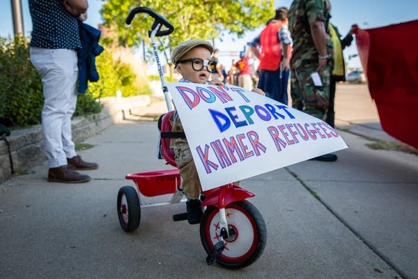 A young boy holds a sign on his trike.