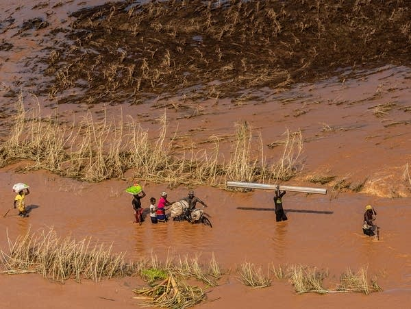 People wade through flood waters from Cyclone Idai