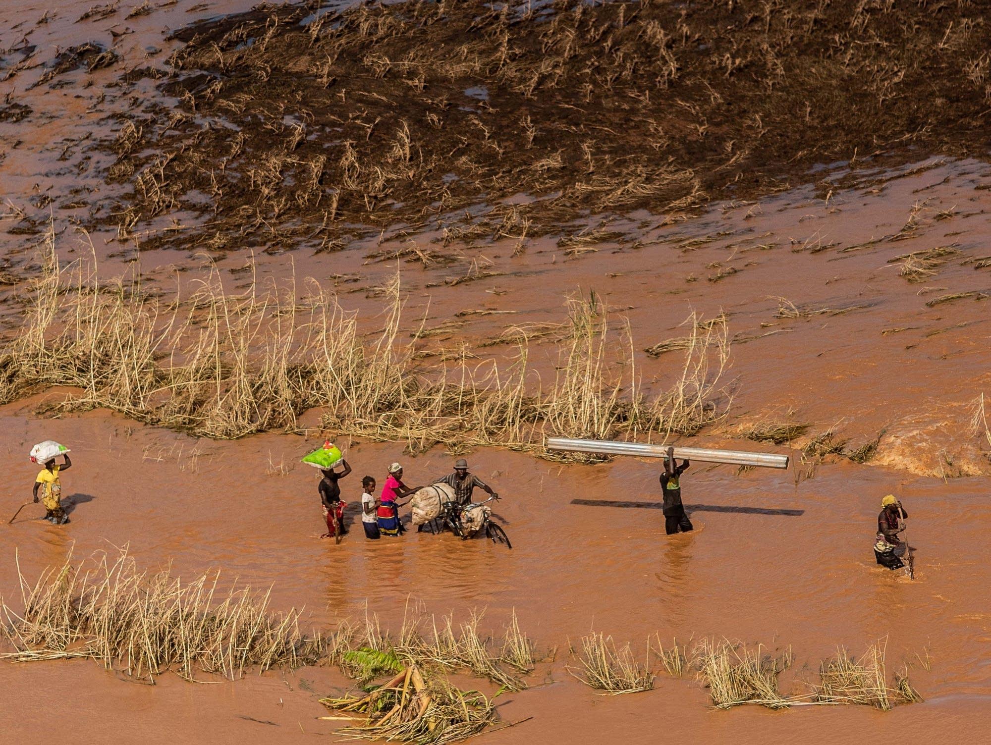 People wade through flood waters from Cyclone Idai