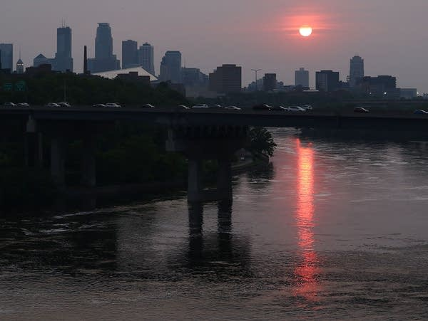 The sun sets over downtown Minneapolis and the Mississippi River