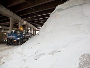 A snow plow drives past a pile of road salt.