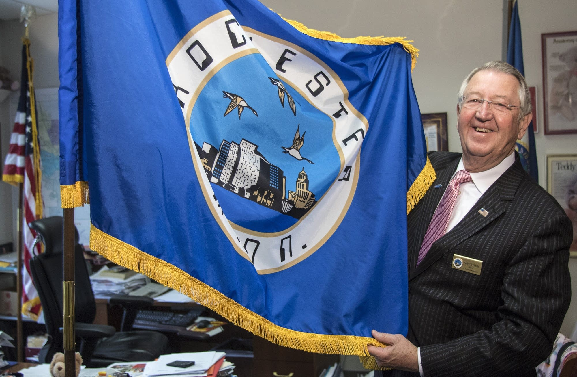 Rochester mayor Ardell Brede displays the city flag in his office.