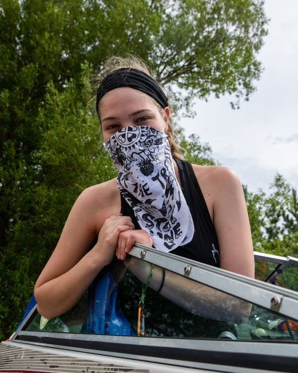 An activist with a face bandana sits in a boat.