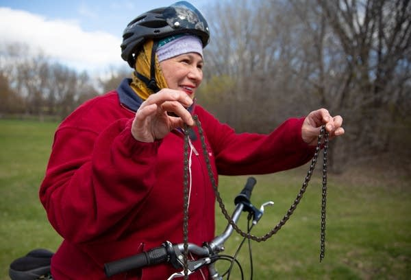 a woman dressed in red holds a bicycle chain