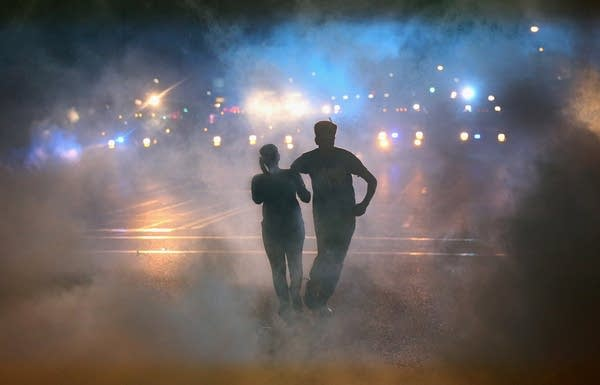 Shadow of two people in a smoke filled street backlit by police lights.