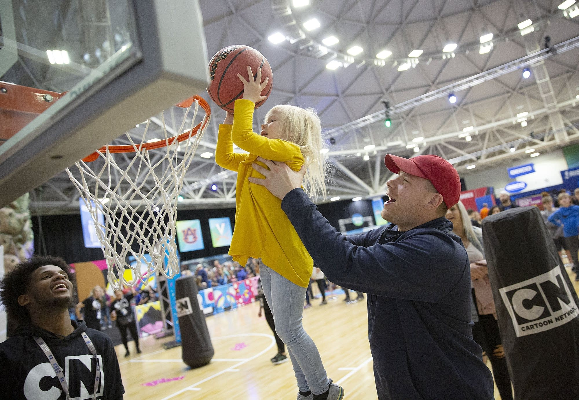 Victor Vondracek helps his 3-year-old daughter, Braelyn, dunk the ball.