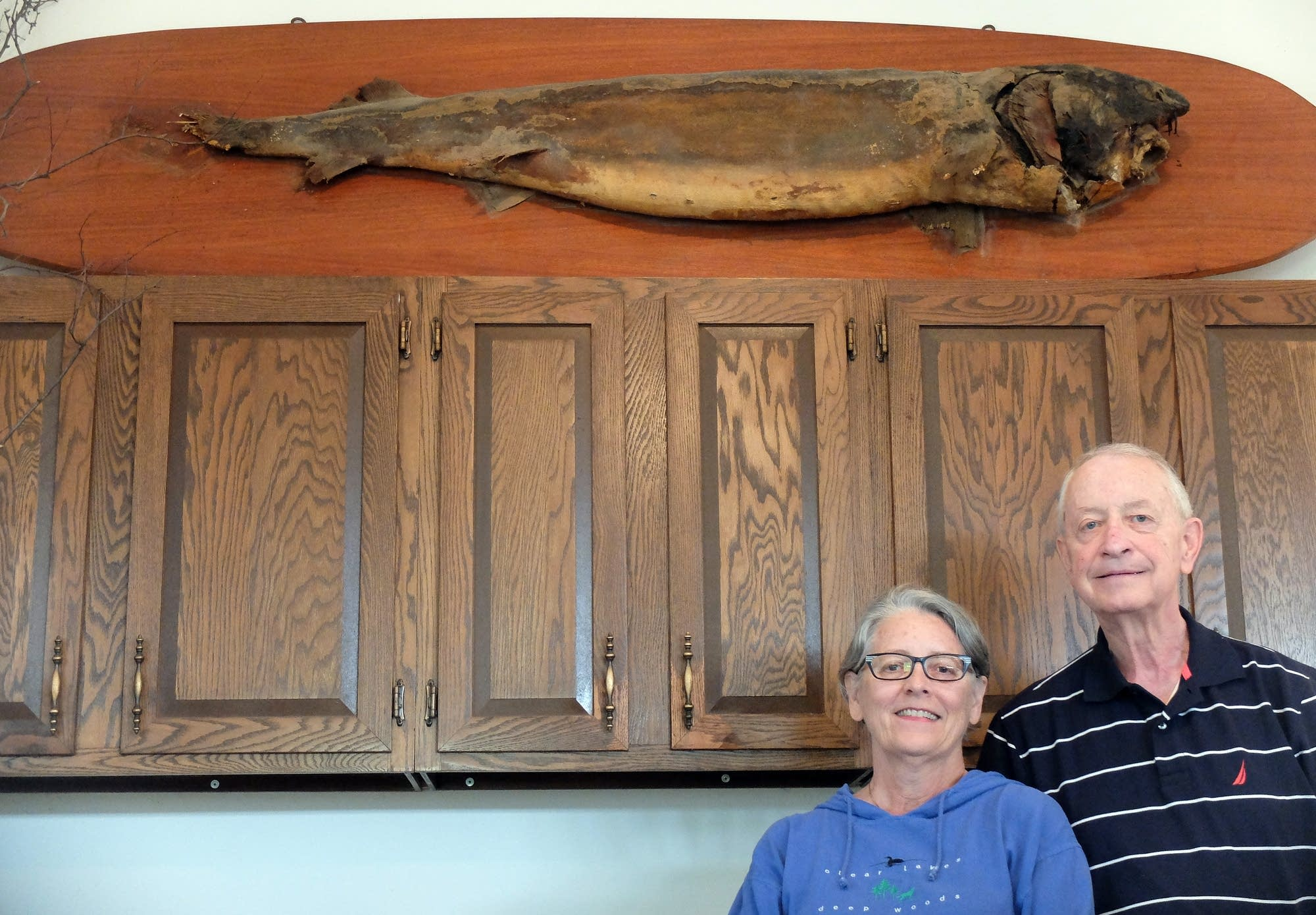 Karen and John Borg stand beneath the original mount of the 1948 sturgeon.