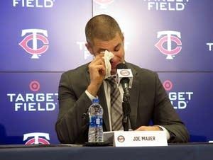 Joe Mauer wipes away a tear at a press conference.