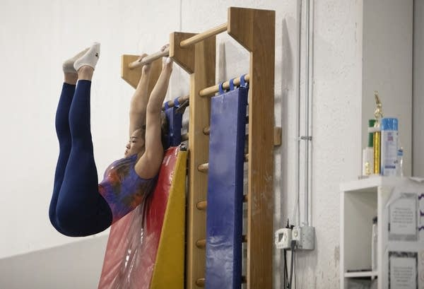 A teen does ab crunches on a pull-up bar attached to a wall.