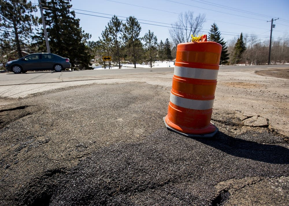 Orange barrels warn motorists about an uneven road