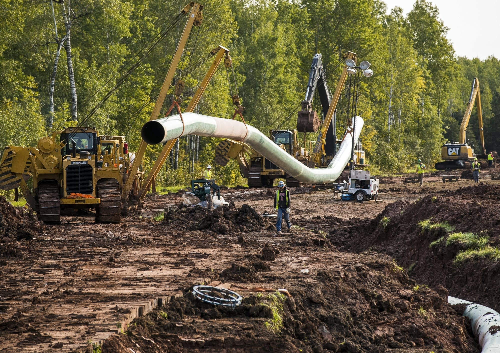 Construction vehicles transport a new section of pipeline.