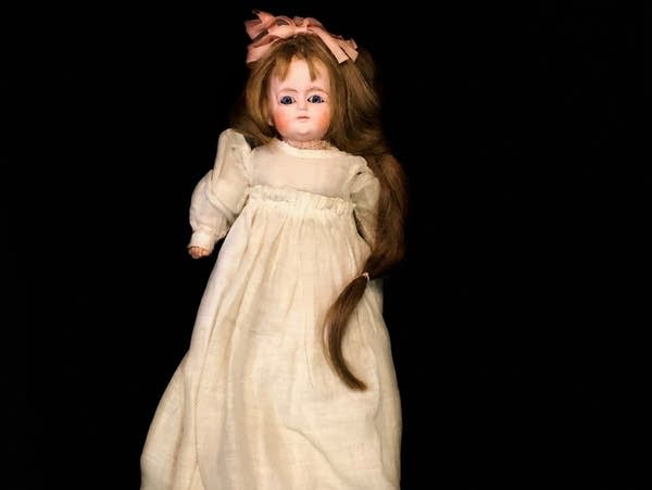 A doll with a long white dress and long hair with a pink bow.