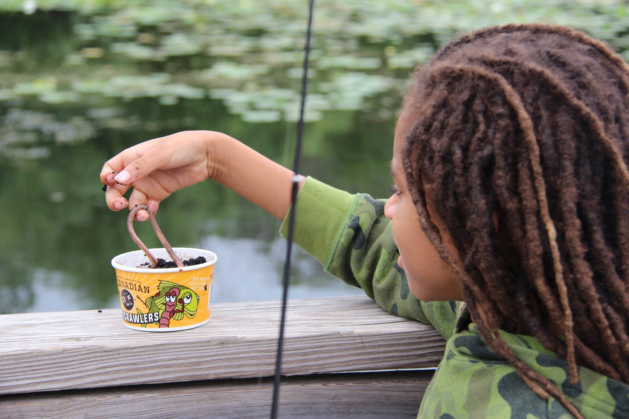 Amitri Hosea picks up a fresh worm while fishing on Lake Snelling.