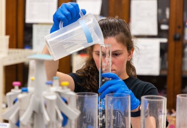 A person pours liquids in a lab setting