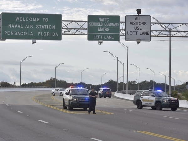 A multi-lane highway sits empty, except for a few police vehicles.