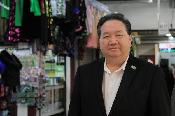 A man wearing a button down shirt and black jacket.