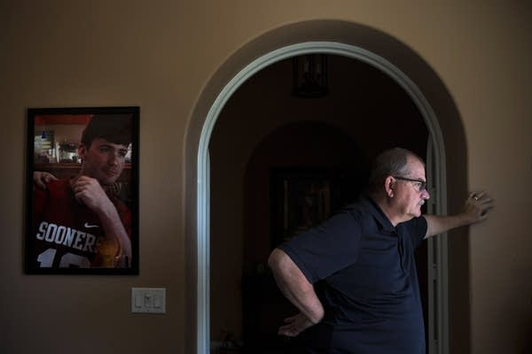 Doug Biggers pauses in his home office next to a photo of his son.