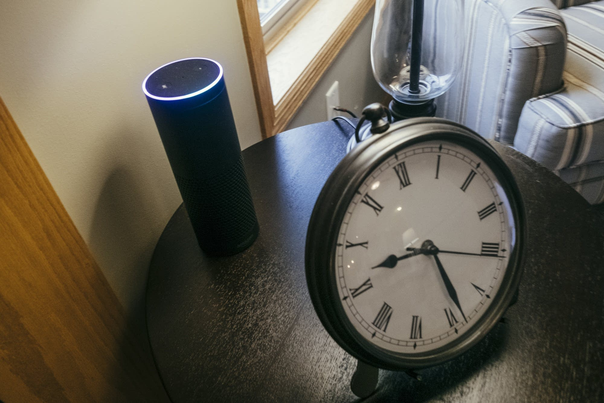An Amazon Echo sits on an end table.