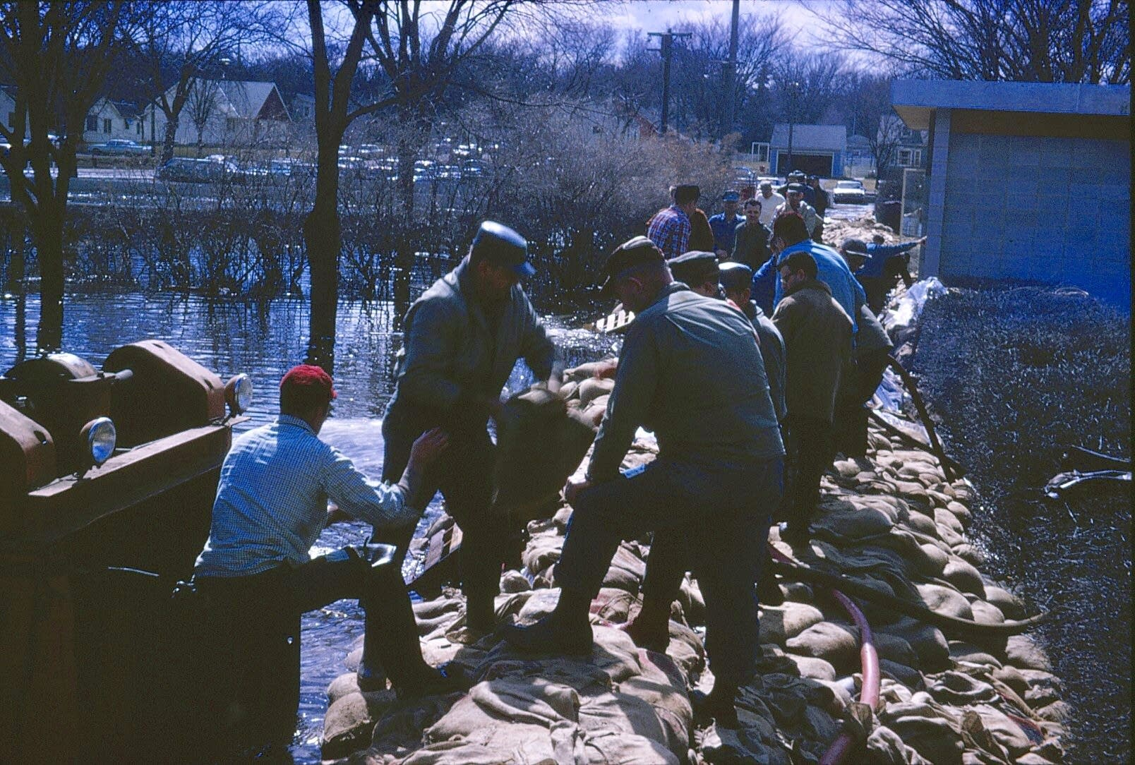 Men stack sandbags on a wall.
