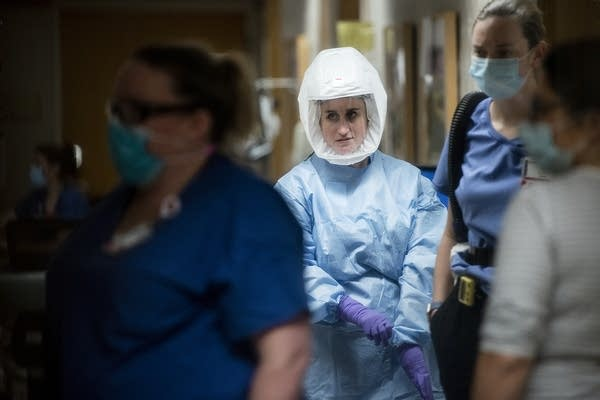 Nurses and doctors walk through a hallway.