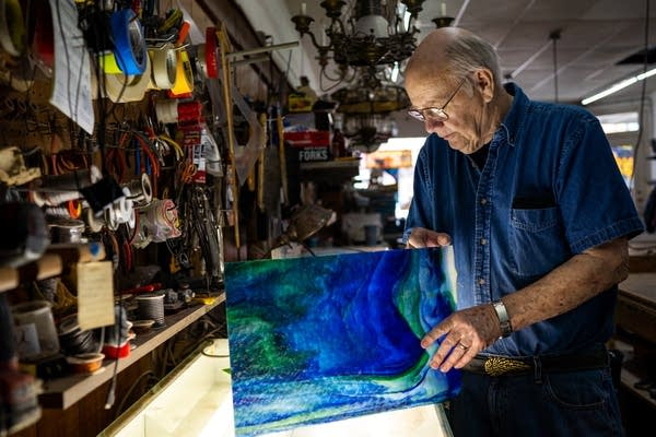 A man stands over a workbench with a piece of blue glass.